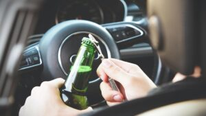 Picture of driver opening a beer bottle for blog about things that impact your auto insurance