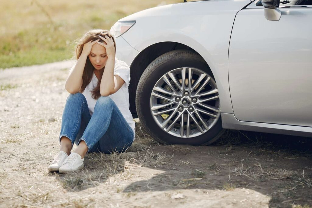 image of tired woman sitting near car for blog about the dangers of drowsy driving