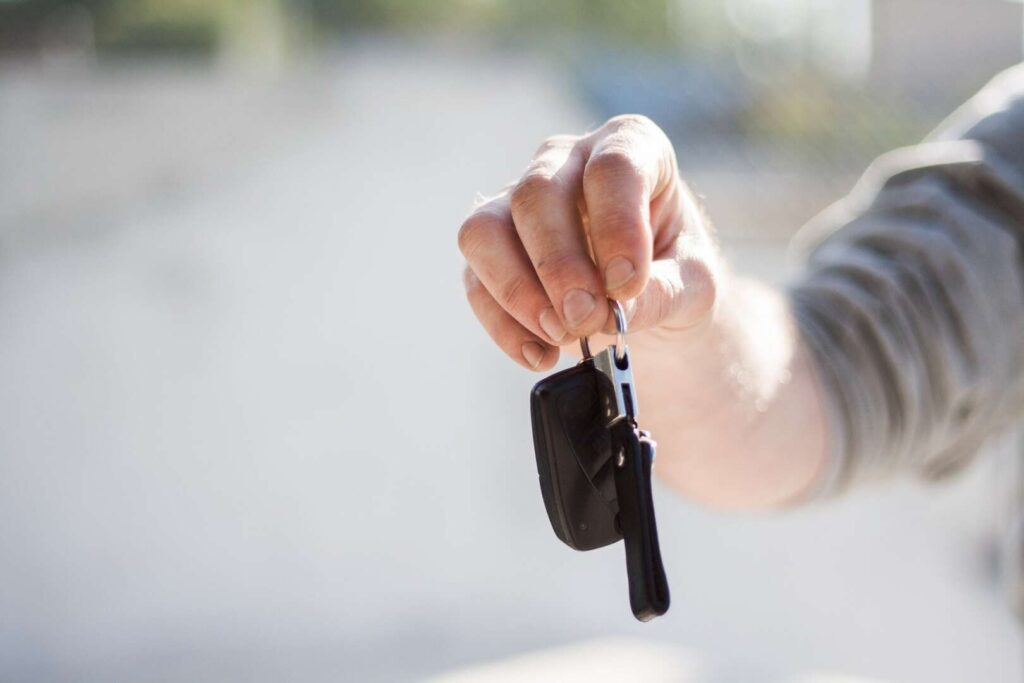 Person handing over car keys for article about what your auto insurance covers when someone borrows your car